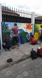 Mateo pintando un mural con estudiantes voluntarios
