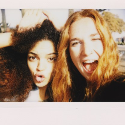 Two women taking a self-portrait with Instant camera