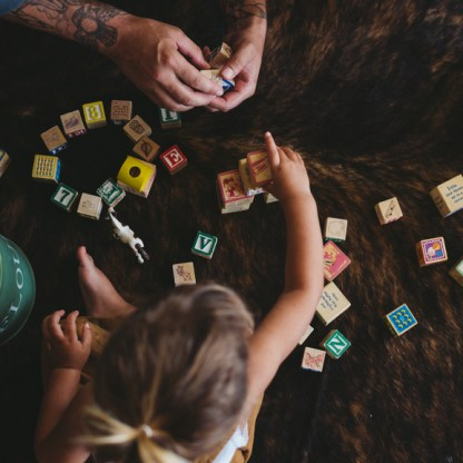 Cute young toddler girl and dad playing with building blocks ins