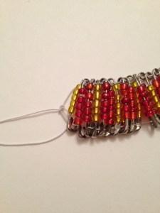 Stringing safety pins onto elastic.