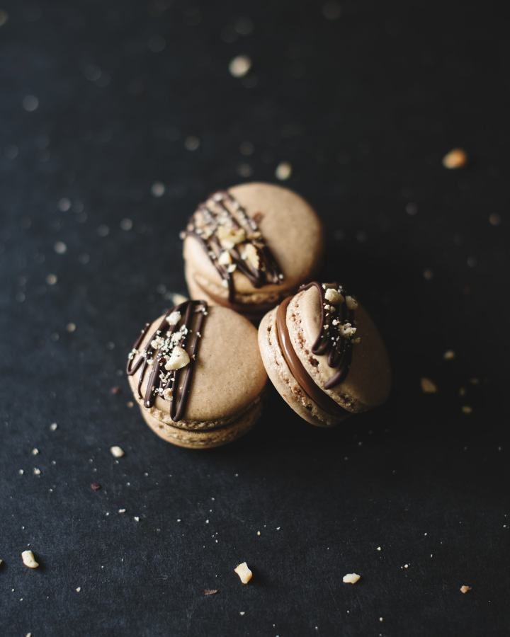 3 Ferrero Rocher macarons on a black background surrounded by crushed hazelnuts