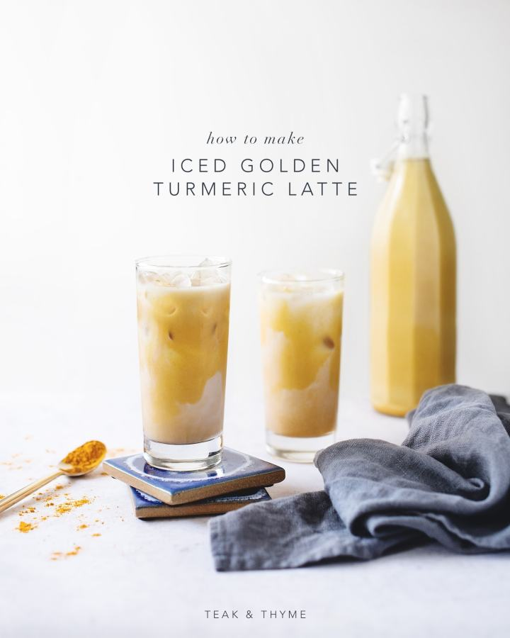 Glasses of iced golden turmeric lattes on blue coaster with blue linen napkin