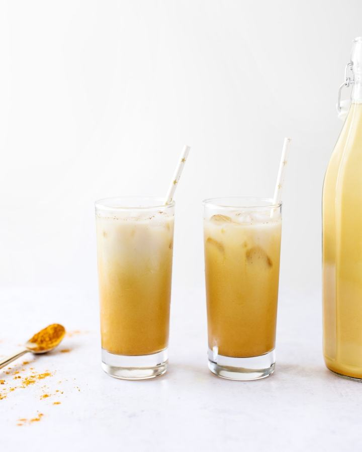 Glasses of iced golden turmeric latte with paper straws and spoon of turmeric