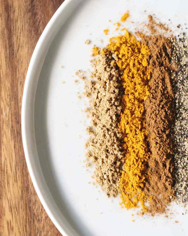 Yellow and orange spices on white plate on wood background
