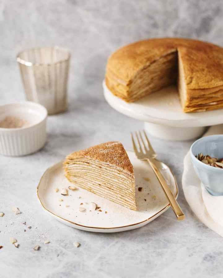 A slice cut out of a pumpkin crepe cake on a white plate