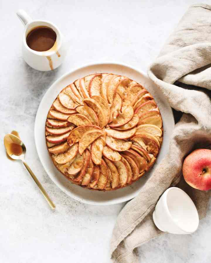 Overhead shot of a spiced apple cake with salted maple caramel drizzle next to a brown linen and spoonful of caramel