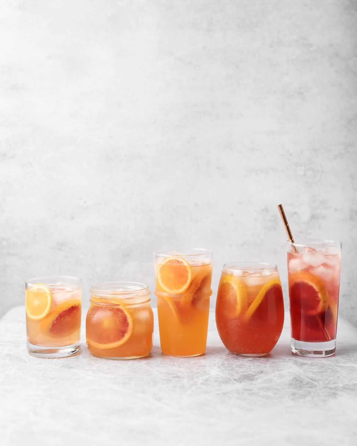 Glasses of blood orange palomas lined up as a gradient on a grey background