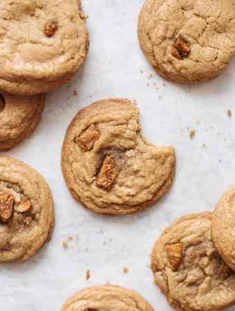 A bite taken out of a cookie surrounded by several cookies