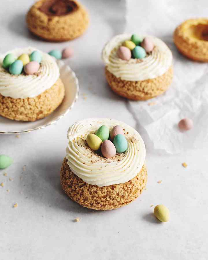 Choux au craquelin mini egg cream puffs that look like nests on plate and parchment