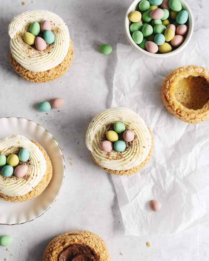 Overhead shot of mini egg cream puffs on parchment with a bowl of mini egg chocolates