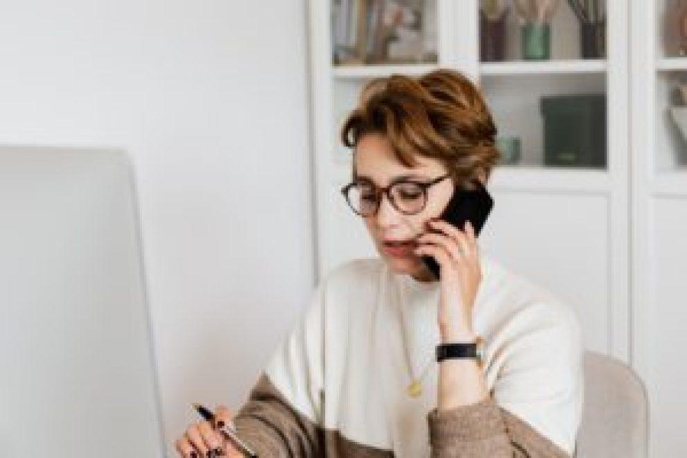Mulher falando ao telefone celular, ela está sentada e em frente a um computador.