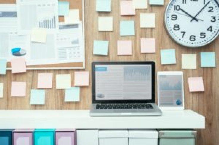 post it e computador em cima da mesa, é um ambiente de escritório cheio de gráficos e papéis.