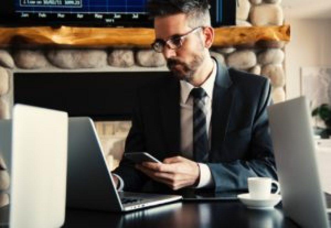 Homem mexendo no celular e no computador ao mesmo tempo, ele veste terno e ao lado tem uma xícara.