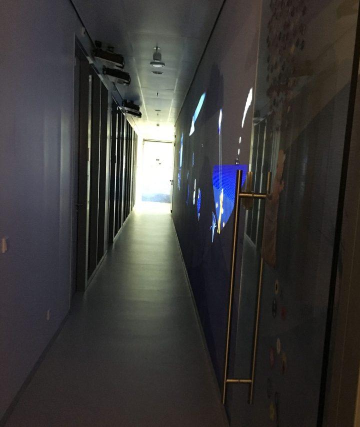 手術室への通路。右側の壁に投影されるアニメーションは、天井のモーションセンサーと連動していて、キャラクターが子供と一緒に手術室へと向かう演出になっています。