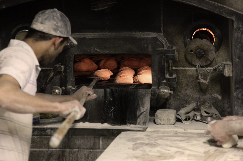 Baker putting bread into an oven