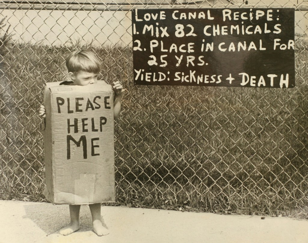 Child and sign protesting the pollution in Love Canal.