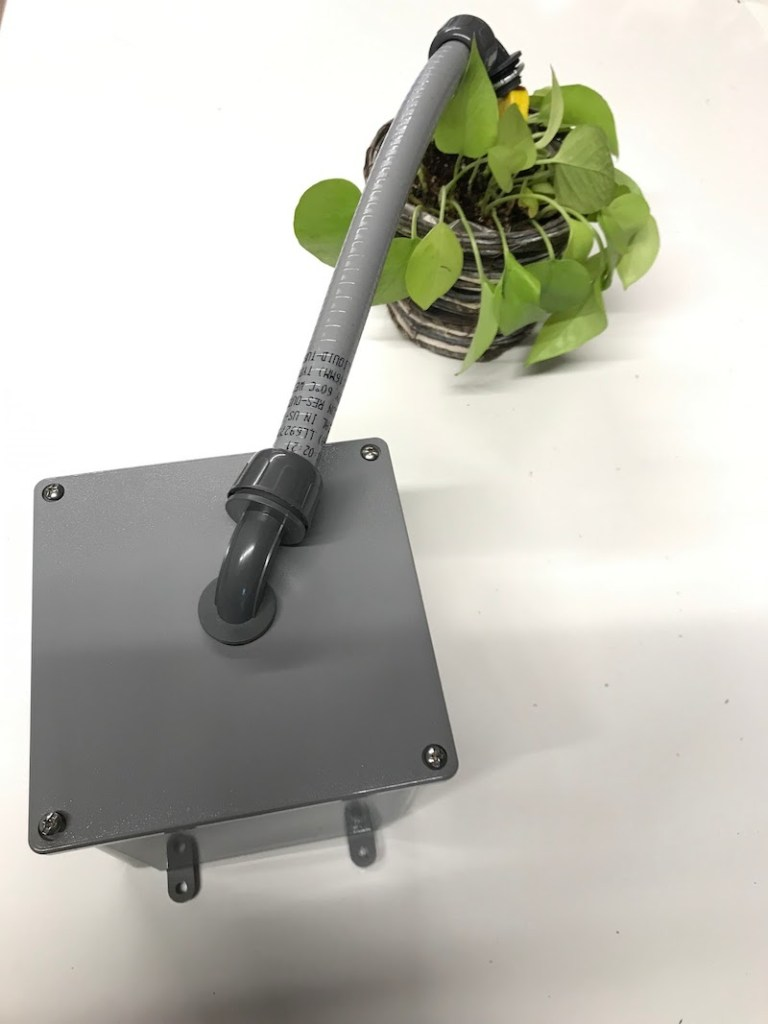 A junction box with one 90 degree conduit attached to the box, a pvc pipe connected to the 90 degree conduit with another 90 degree conduit at the end of the pvc pipe for soil moisture monitoring system