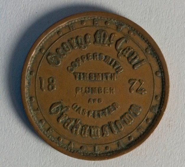 Obverse of token issued by George McCaul, 1874, Thames, maker unknown. Te Papa (NU002475)