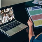 Person participating in virtual meeting on laptop, holding clipboard with feedback worksheet.