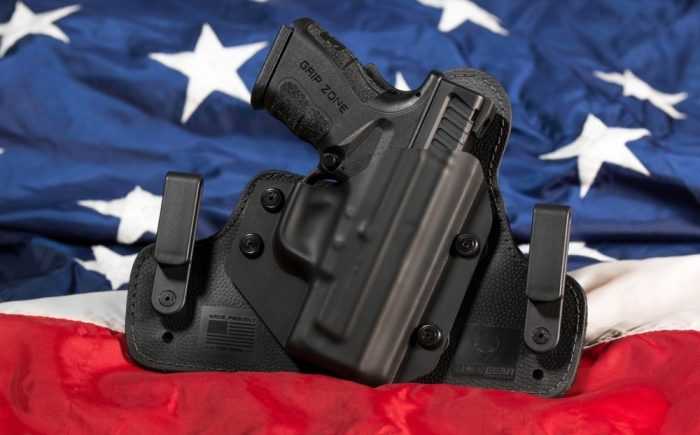 pistol in a black Kydex holster atop an American Flag to support constitutional carry laws