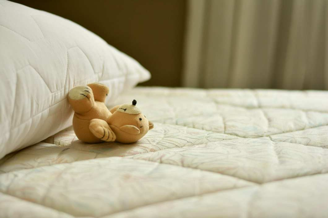 A bare mattress and pillow with a teddy bear laying on it.