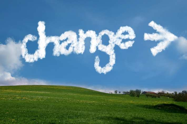 "A landscape with the word ""CHANGE,"" along with an arrow pointing to the right, written in the clouds."