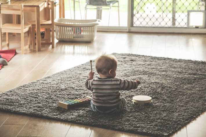 An infant playing with musical instruments.