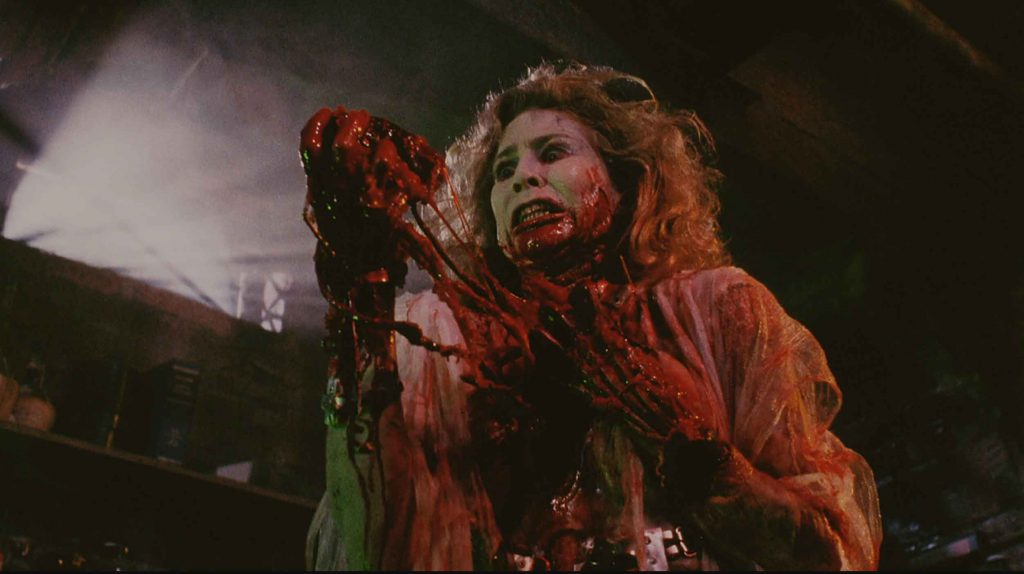 A scene where the living bride of the re-animator pulls her own, or someone's, heart out of her chest from Bride of Re-Animator