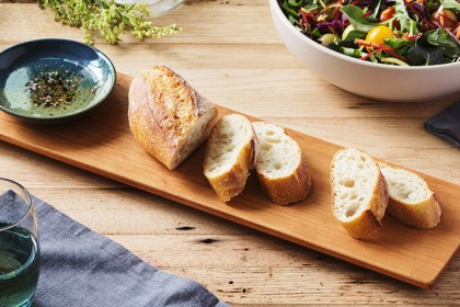 Sliced bread on a wood board with a ceramic bowl of olive oil for dipping.