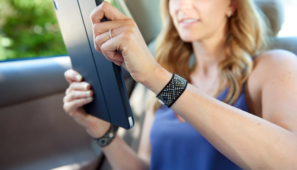 A woman is seen reading on a tablet in the car wearing Blisslets anti-nausea pressure bracelets