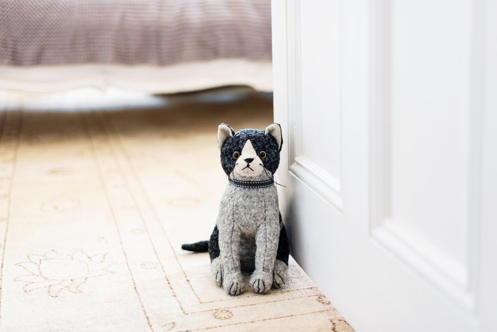 A whimsical stuffed cat doorstop from Dora Designs holds a door open