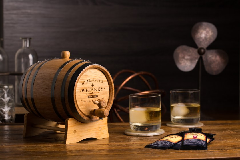 A personalized oak barrel from Thousand Oaks Barrel sits next to 2 glasses of whiskey, the barrel personalized with Williamson's Whiskey