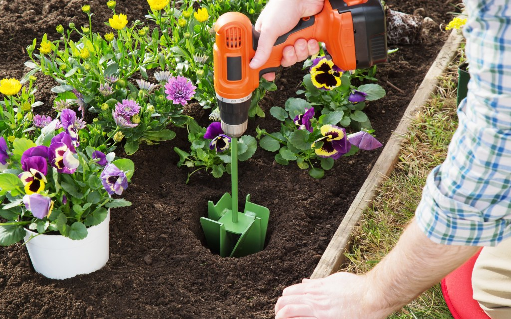 A man drills a hole in his garden using a MAXBIT garden hole digging drill bit