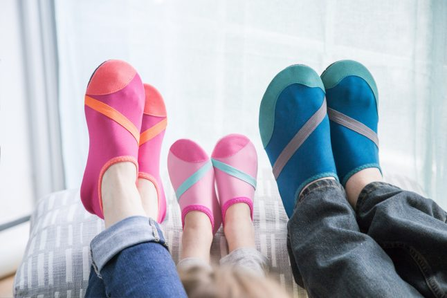 A trio of family's feet can be seen lounging in multicolored Fitkicks athleisure footwear