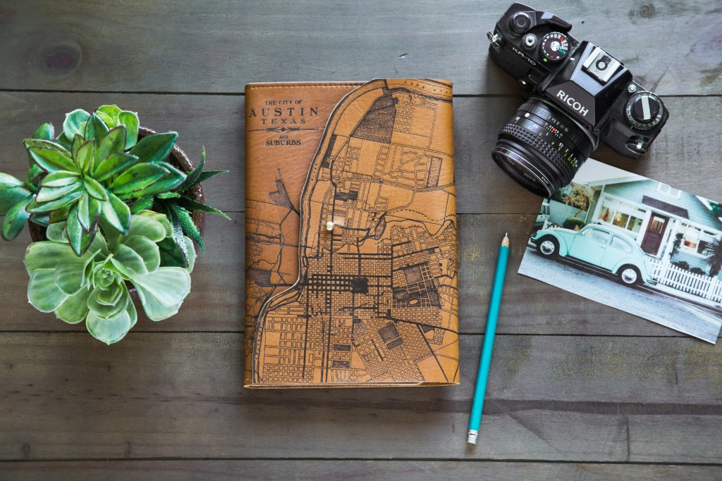 An etched leather map of Austin, Texas appears on a journal from Tactile Craftworks next to a plant and a camera