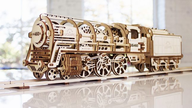 a 3D wooden model of a train from UGEARS sits on a table
