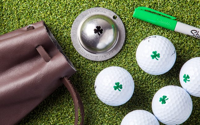 Several white golf balls are marked with a green clover sitting on turf next to Tin Cup's alpha players golf ball marker