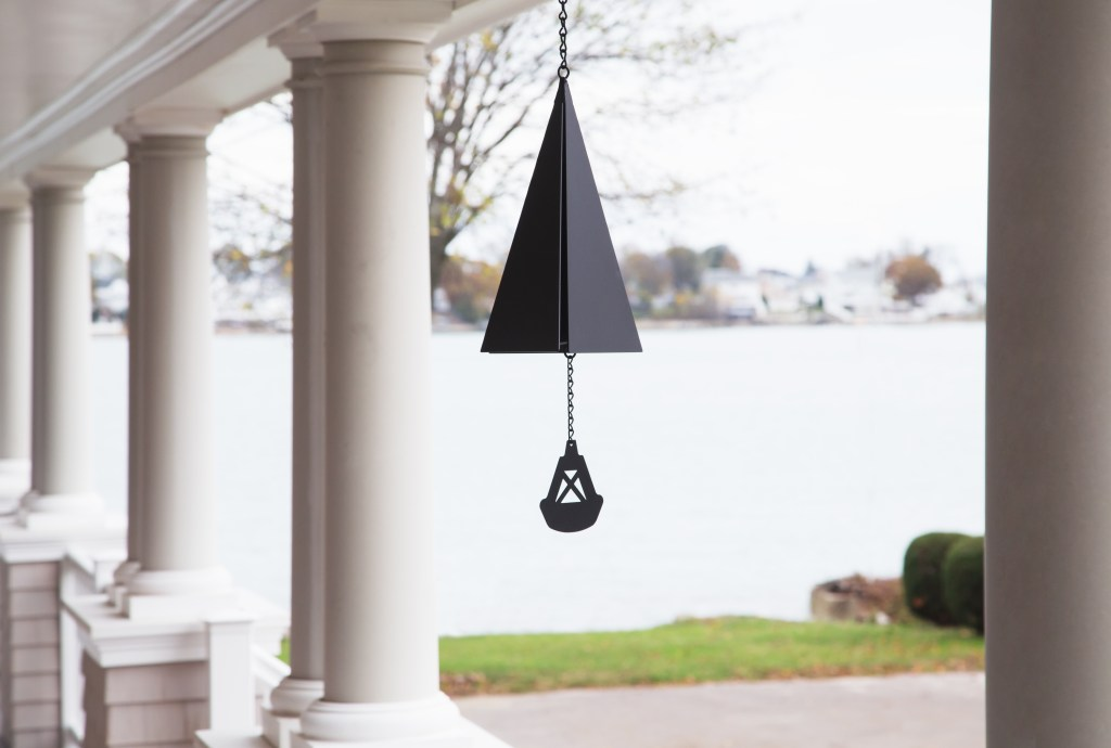 a black buoy bell with buoy charm from North Country Wind Bells hangs from the front porch of a lake house