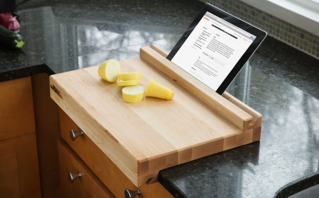 Slices of summer squash and a tablet with a recipe pulled up are seen sitting on a tablet-holding cutting board from Brooklyn Butcher Blocks