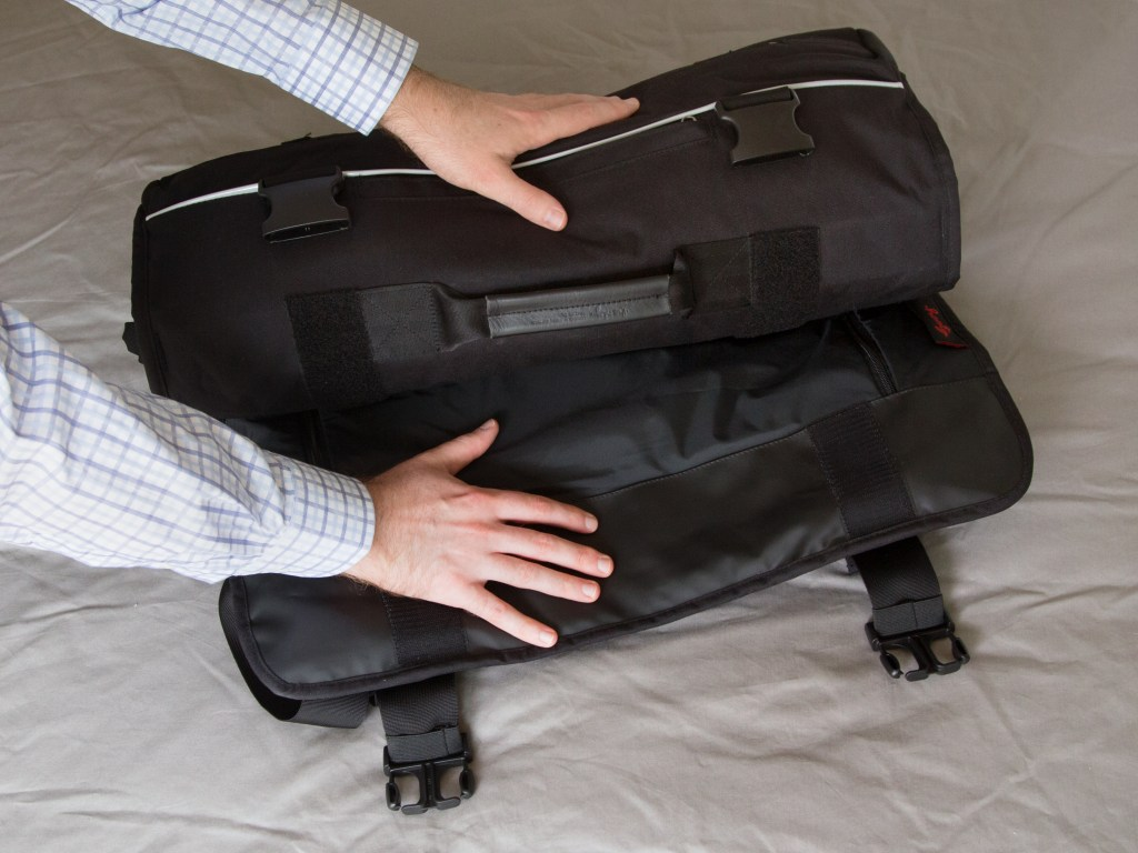 A man is seen rolling up a Henty roll-up suit messenger bag