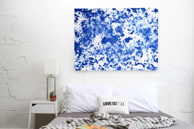 A blue and white abstract painting is seen hanging above a bed, made using LOVE IS ART's intimate painting kit