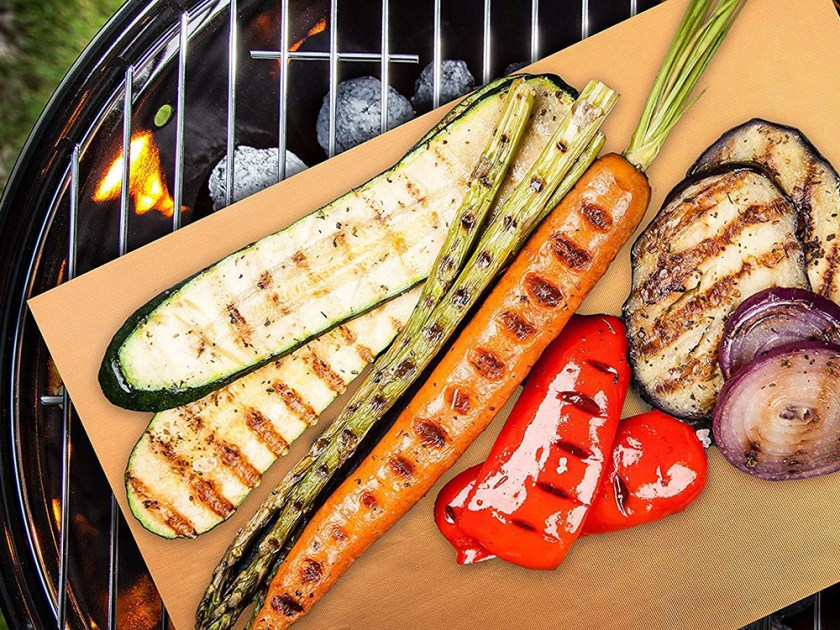 A variety of grilled veggies sits on top of a copper grill mat from Bear Paw over a charcoal grill