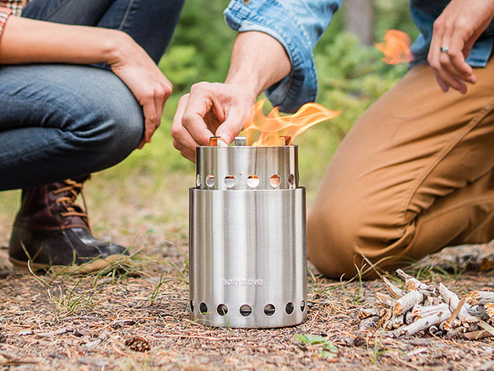 A couple lights a fire in the woods with Solo Stove's Titan portable wood stove