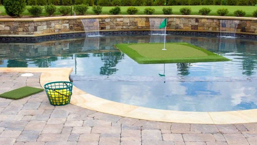 A putting green from Floating Golf Greens floats in an inground pool with a bucket of golf balls ready on the patio