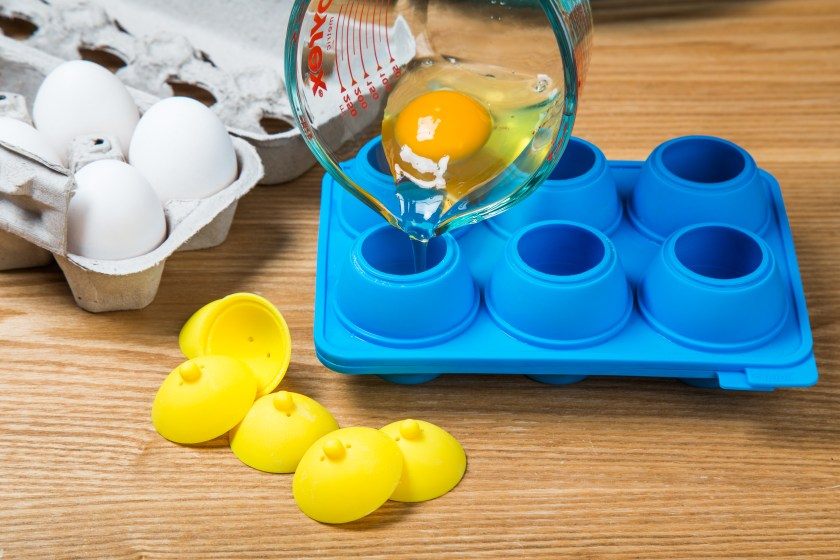 A measuring cup is used to pour a faw egg into  silicone egg mold