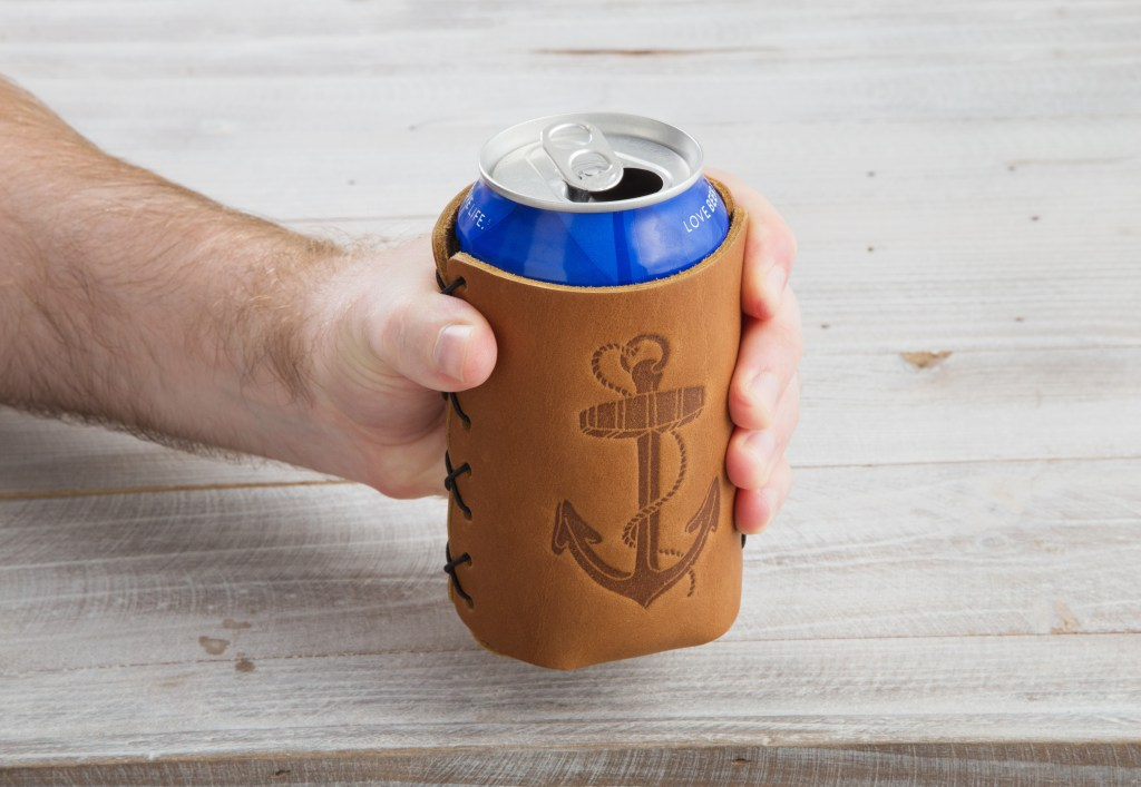 A man holds a can of beer tucked nicely into a tan leather can sleeve adorned with an anchor from Oowee