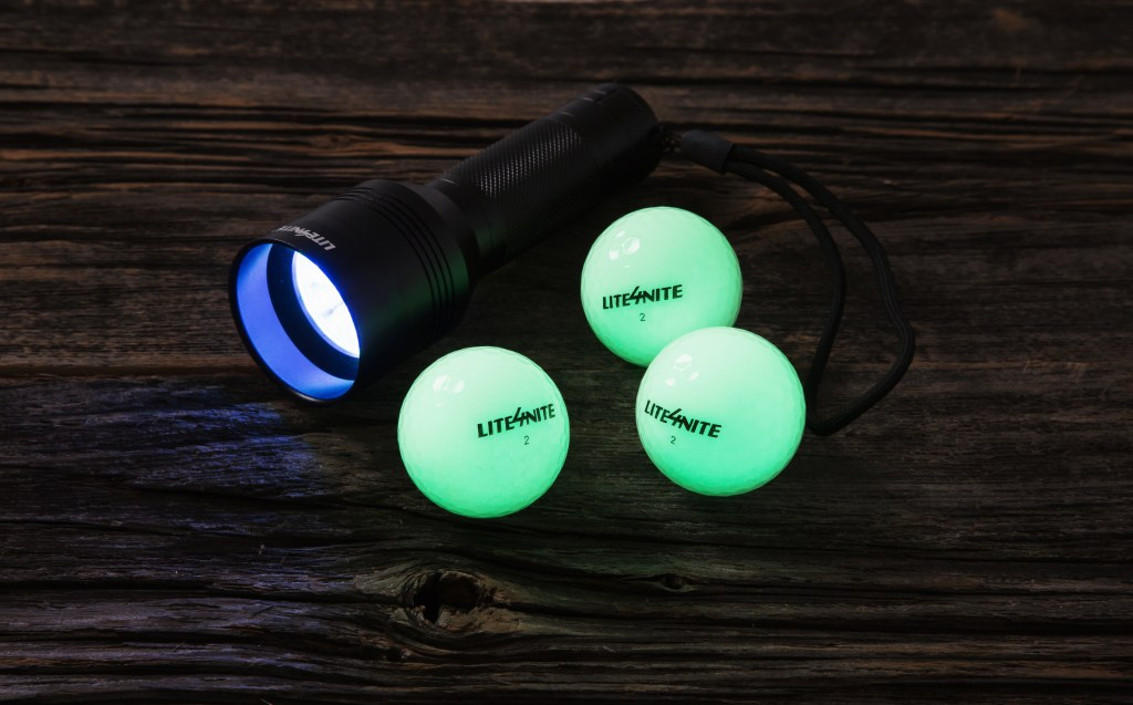 3 glow in the dark golf balls from Lite4Nite sit on a table next to a flashlight
