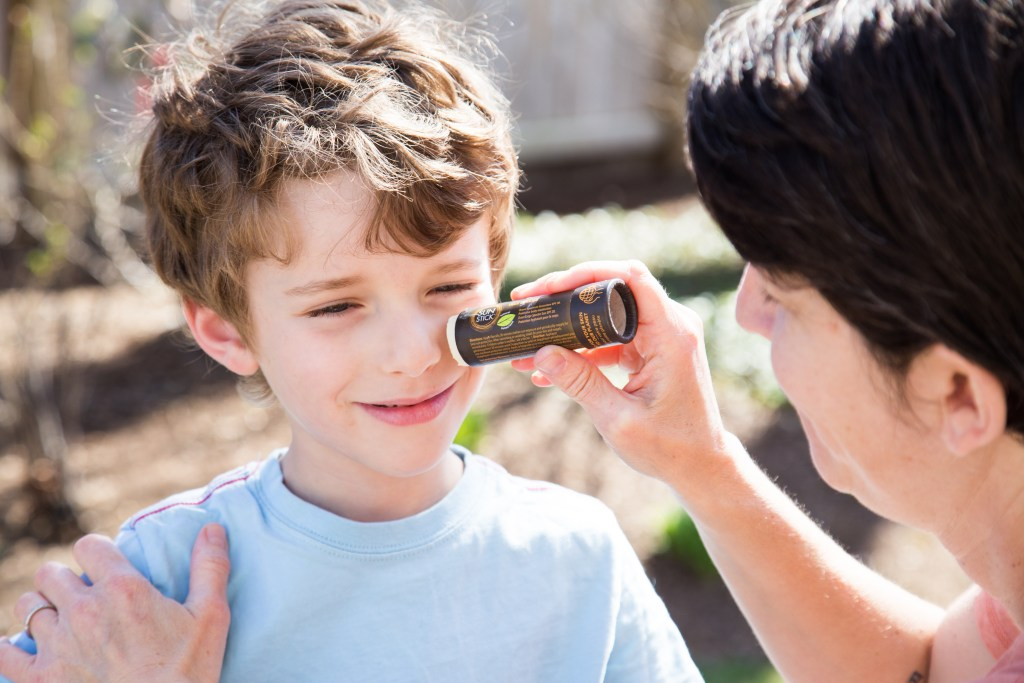A mom applies Dr. Federenko's organic sun stick to her son's face