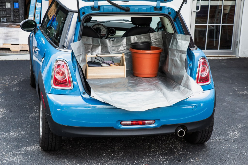 A blue car has its trunk open to reveal tools sitting on a full coverage cargo liner from CarGo Apron