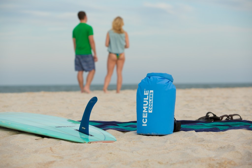 A blue IceMule classic cooler sits on a beach with a couple in the distance